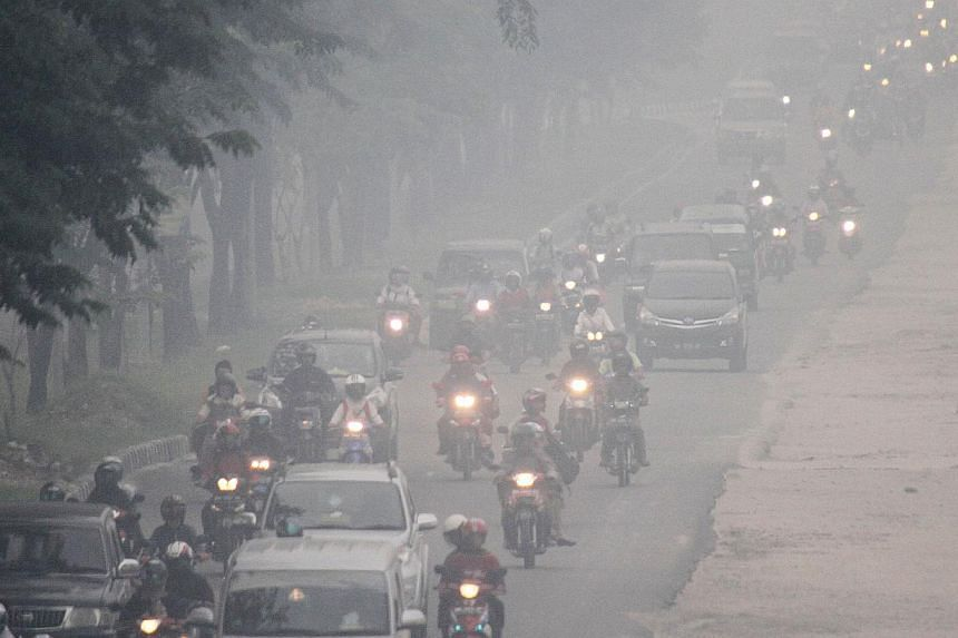 Thick haze blanketing a road in Pekanbaru in Riau yesterday. Environment Minister Balthasar Kambuaya told Parliament the move to ratify the pact would benefit Indonesia the most as it would better protect its citizens from the effects of forest fires