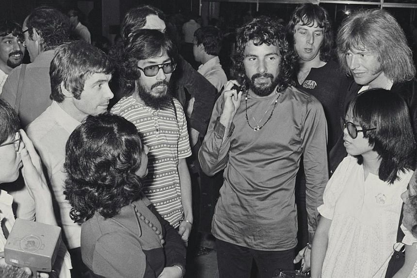 Cat Stevens, (centre, in long sleeve shirt), and his nine-man band at the Singapore airport, where he stopped over on the way to perform in Tokyo in 1972. -- PHOTO: ST FILE