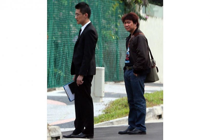 Former China tour guide Yang Yin (right) and his lawyer (left) outside the bungalow of 87-year-old widow Madam Chung Khin Chun. -- ST PHOTO: NEO XIAOBIN