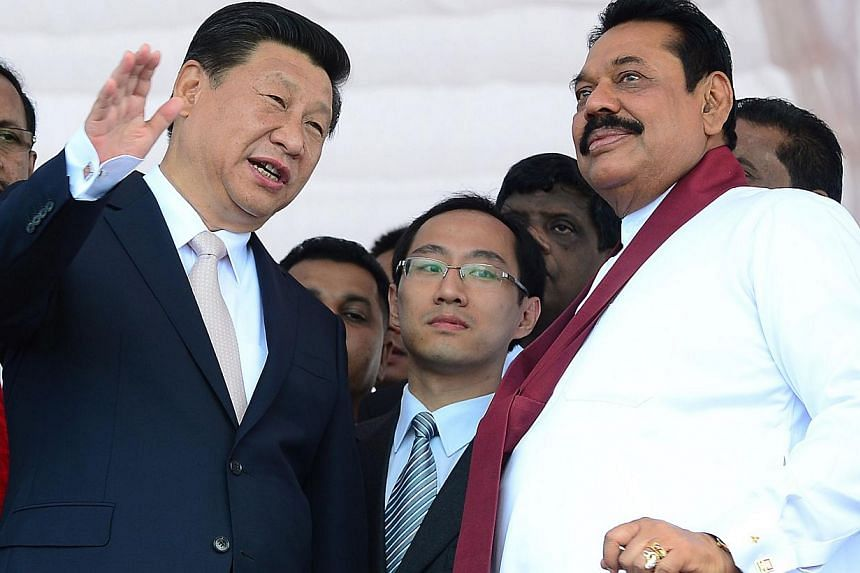 Chinese President Xi Jinping (left) speaks with Sri Lankan President Mahinda Rajapakse (right) as he formally launched the construction of a Chinese-funded US$1.4 billion (S$1.77 billion)port city on the last day of his visit to Sri Lanka in Co