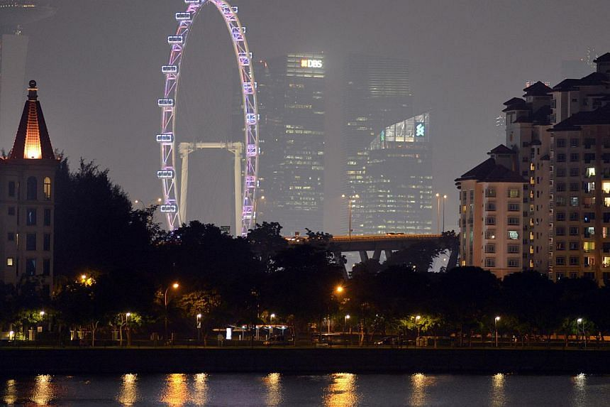 Singapore skyline at 9.45pm showing slightly clearer skies. The PSI at 9pm was 100, but had fallen to just within the moderate range at 99 by 10pm. -- ST PHOTO:LIM SIN THAI