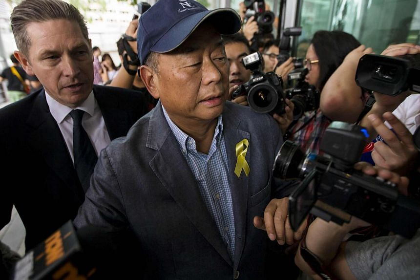 Jimmy Lai (right), owner of Hong Kong-based media company Next Media Ltd, arrives at the Independent Commission Against Corruption (ICAC) headquarters in Hong Kong on Sept 17, 2014. -- PHOTO: REUTERS