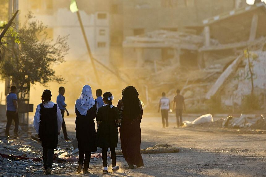Palestinian girls walk past buildings which were destroyed by Israeli strikes on their way to school in the Shejaiya neighbourhood of Gaza City on Sept 14, 2014 on the first day of the new school year. -- PHOTO: AFP
