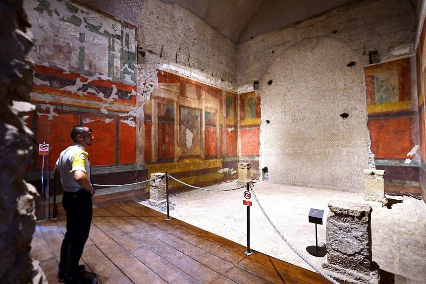 Security man stand inside a room at the House of Augustus on the Palatine hill in Rome on Sept 17, 2014.Lavishly frescoed rooms in the houses of the Roman Emperor Augustus and his wife Livia are opening for the first time to the public Thursday