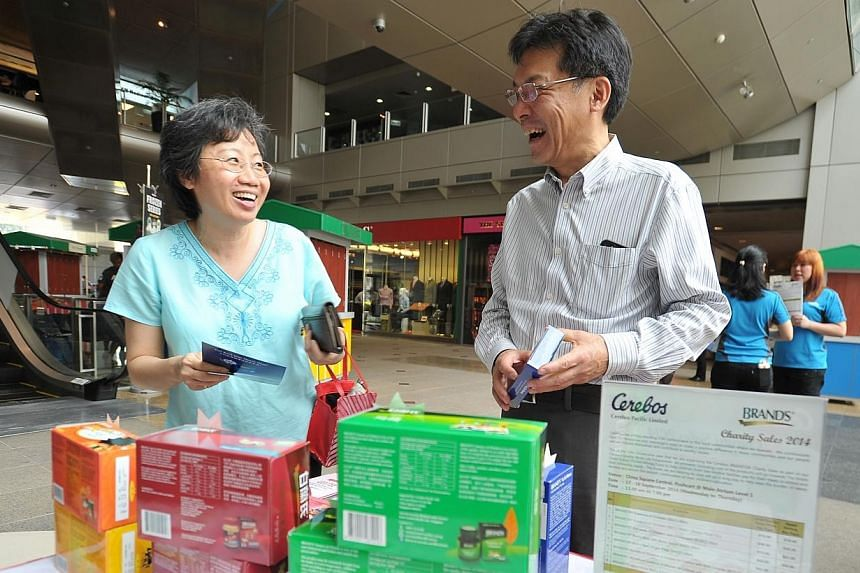 A customer with Cerebos chief executive officer, Mr Gen Saito, at the company's annual charity sale booth at China Square Central on Sept 17, 2014. -- PHOTO: LIM YAOHUI FOR THE STRAITS TIMES