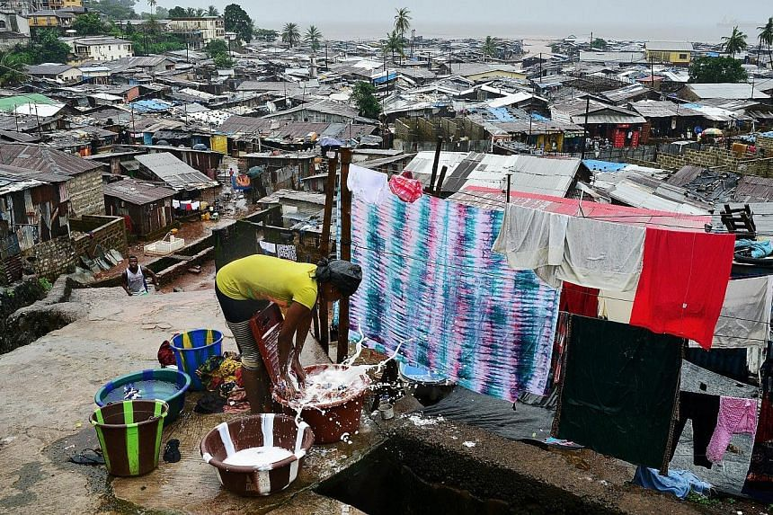 A woman washes clothes in the Kroo town slum in Freetown on Aug 13, 2014.Sierra Leone prepared Thursday for an unprecedented three-day nationwide lockdown to contain the deadly spread of the Ebola virus in a controversial move which experts cla