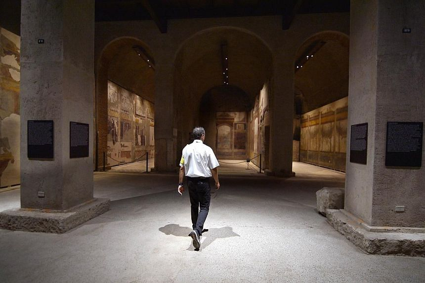 A security man walks inside a room at the House of Augustus on the Palatine hill in Rome on Sept 17, 2014.Lavishly frescoed rooms in the houses of the Roman Emperor Augustus and his wife Livia are opening for the first time to the public Thursd
