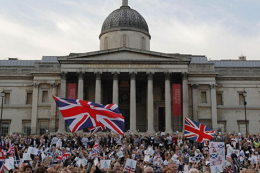 Pro-union supporters, opposing Scottish independence from the United Kingdom wave flags during a rally in Trafalgar Square in London on Sept 15, 2014, ahead of the Scottish independence referendum. -- PHOTO: AFP
