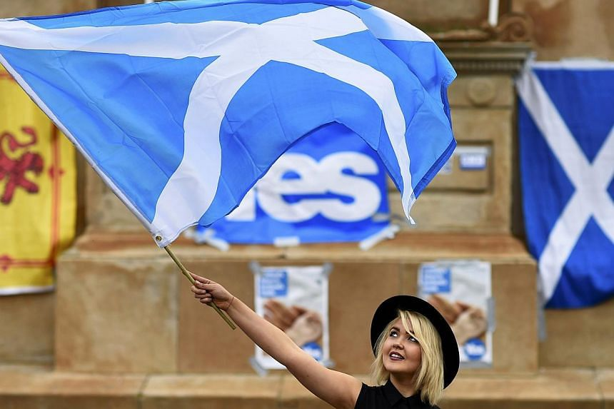A woman waves a Scottish Saltire at a 'Yes' campaign rally in Glasgow, Scotland Sept 17, 2014. -- PHOTO: REUTERS