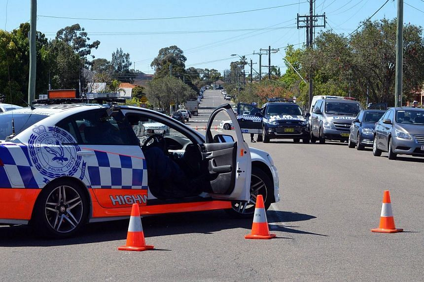 Police and other law enforcment agencies cordon off a street as forensic experts collect evidence inside a house in the Guildford area of Sydney on Sept 18, 2014. -- PHOTO: AFP