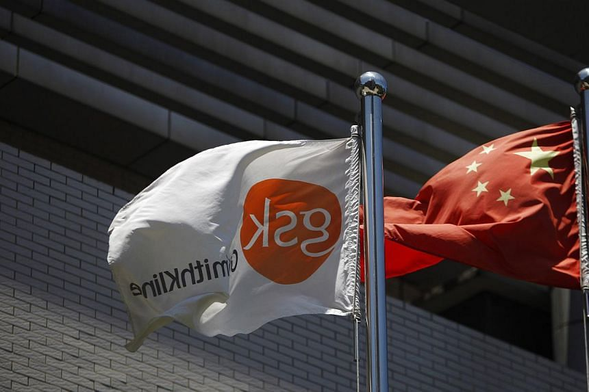 A flag (left) bearing the logo of GlaxoSmithKline (GSK) flutters next to a Chinese national flag outside a GlaxoSmithKline office building in Shanghai in this July 12, 2013, file photo.A Chinese court on Friday fined British drugmaker GlaxoSmit