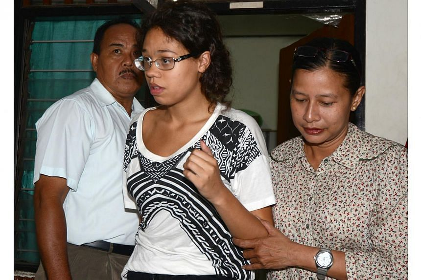 A police officer escorts suspect Lois Heather, 19, (centre) during an investigation at a police office in Nusa Dua on Indonesian resort island of Bali on Aug 13, 2014, after an American tourist's battered body was found in a suitcase at an exclusive