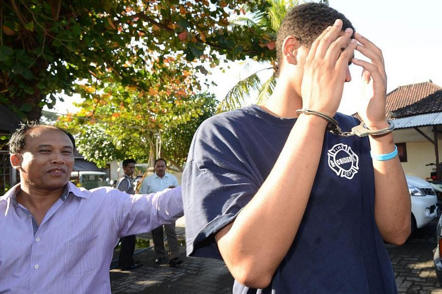 A police officer escorts suspect Tommy Schaffer, 21, (right) during an investigation at a police office in Nusa Dua on Indonesian resort island of Bali on Aug 13, 2014, after an American tourist's battered body was found in a suitcase at an exclusive