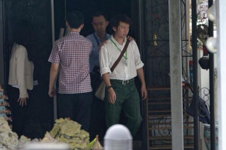 Former tour guide Yang Yin leaving the house at Gerald Crescent on Sept 19, 2014. He was brought back to the cantonment police complex. -- ST PHOTO: NG SOR LUAN