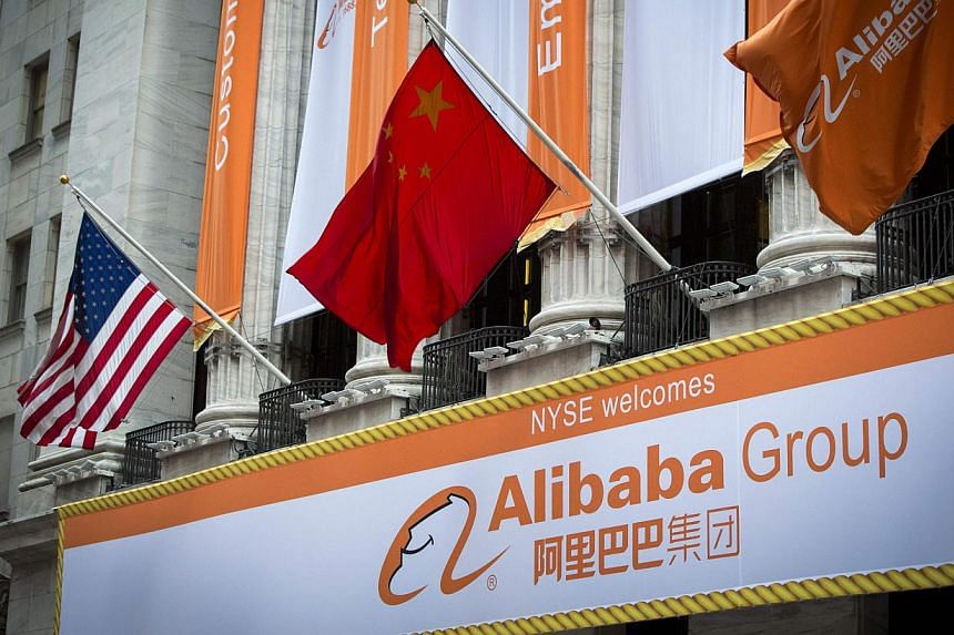 """The Chinese (centre) and US (right) flags fly over signs of Alibaba Group Holding Ltd hung on the facade in front of the New York Stock Exchange before the company's initial public offering (IPO) under the ticker """"BABA"""" in New York on Sept 19, 2014."""