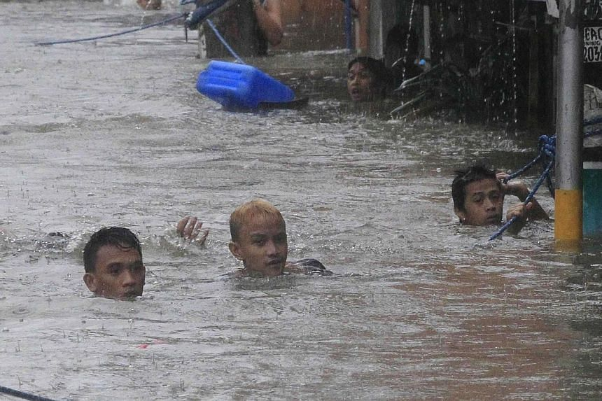 Residents swim in a flooded area to get to another street after tropical storm Fung-Wong battered metro Manila on Sept 19, 2014. -- PHOTO: REUTERS
