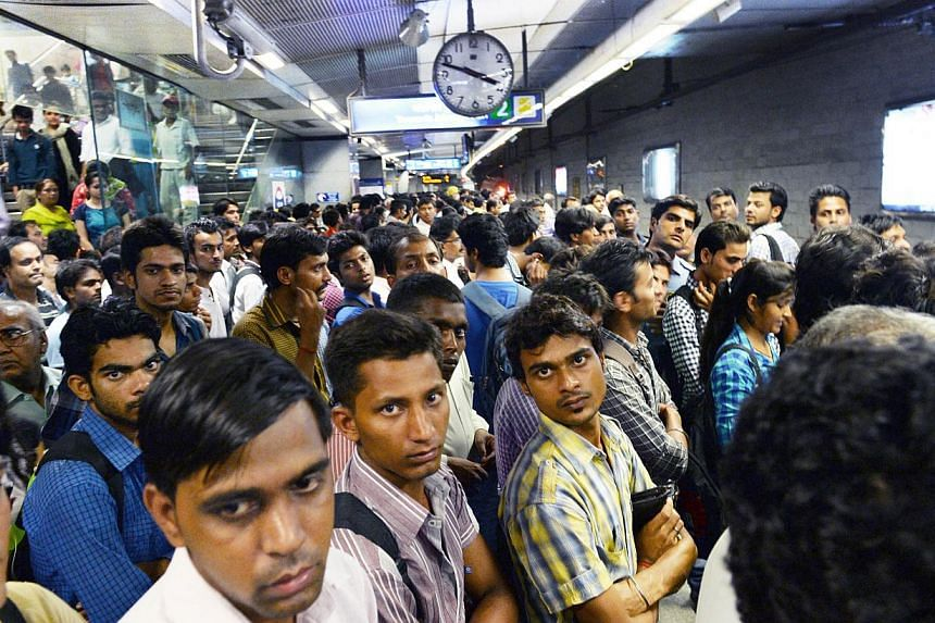 Commuters waiting on a station platform for the metro train in New Delhi on the occasion of World Population Day onJuly 11, 2014.The world population may grow larger than previously estimated, reaching 11 billion people by century's end,
