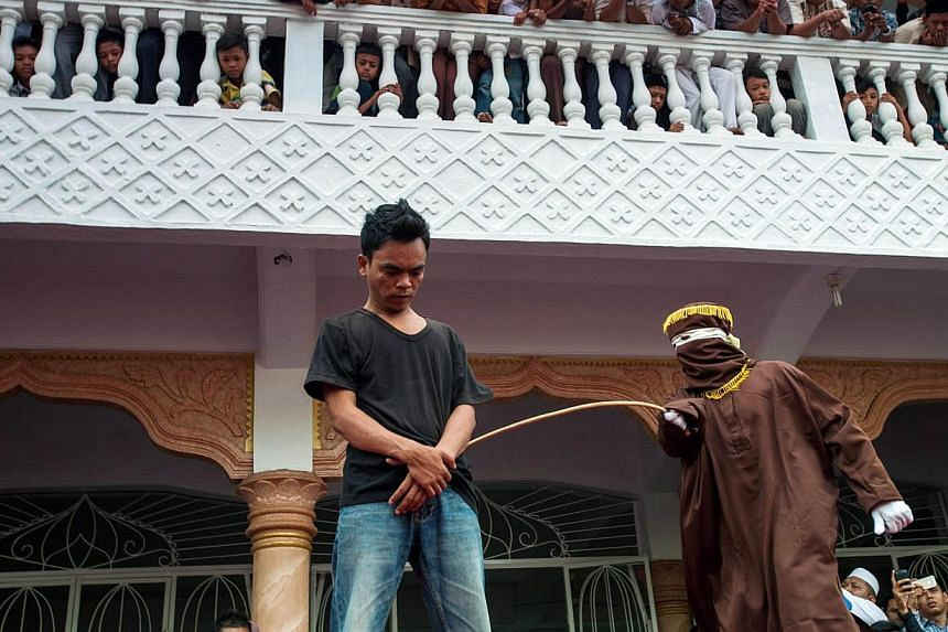 A masked and hooded official (right) canes an Acehnese man for gambling in Banda Aceh on Sept 19, 2014. Gay sex could be punishable by 100 lashes of the cane in Indonesia's staunchly conservative Aceh province if Parliament passes a draft law that cr