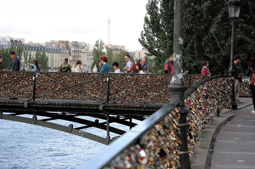 This picture taken on Aug 14, 2014 shows love padlocks attached on the railings of the Pont des Arts in Paris. -- PHOTO: AFP