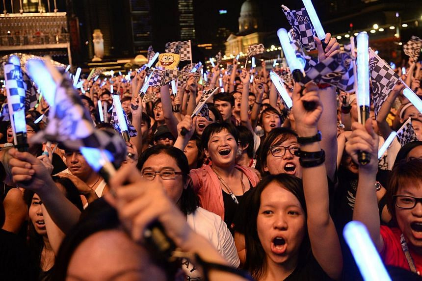 Concert attendees sing and wave their lightsticks during Taiwanese band Mayday's performance at the Padang Stage at the 2014 Formula One Singapore Airlines Singapore Grand Prix on Sept 19, 2014. -- ST PHOTO: MARK CHEONG