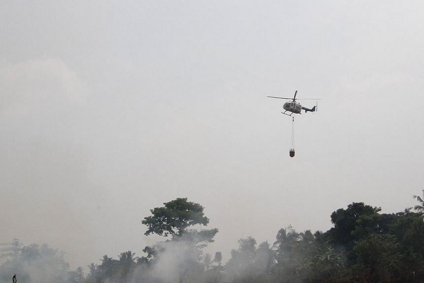 A helicopter operated by Indonesia's disaster mitigation agency conducting water bombing in Ogan Ilir, South Sumatra, yesterday.