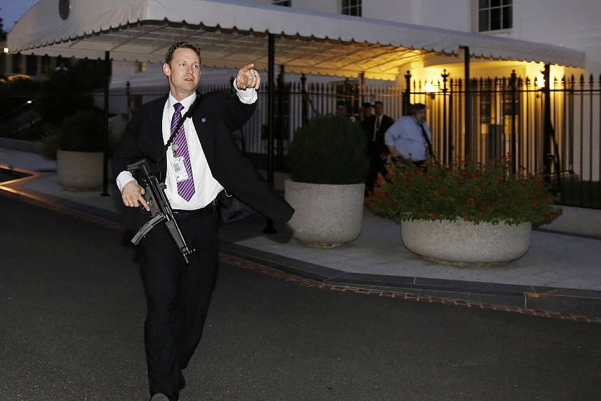 A US Secret Service agent with an automatic rifle hurries people to evacuate the White House complex over a security alert moments after President Barack Obama and his family left for the presidential retreat, Camp David, in Maryland on Sept 19, 2014