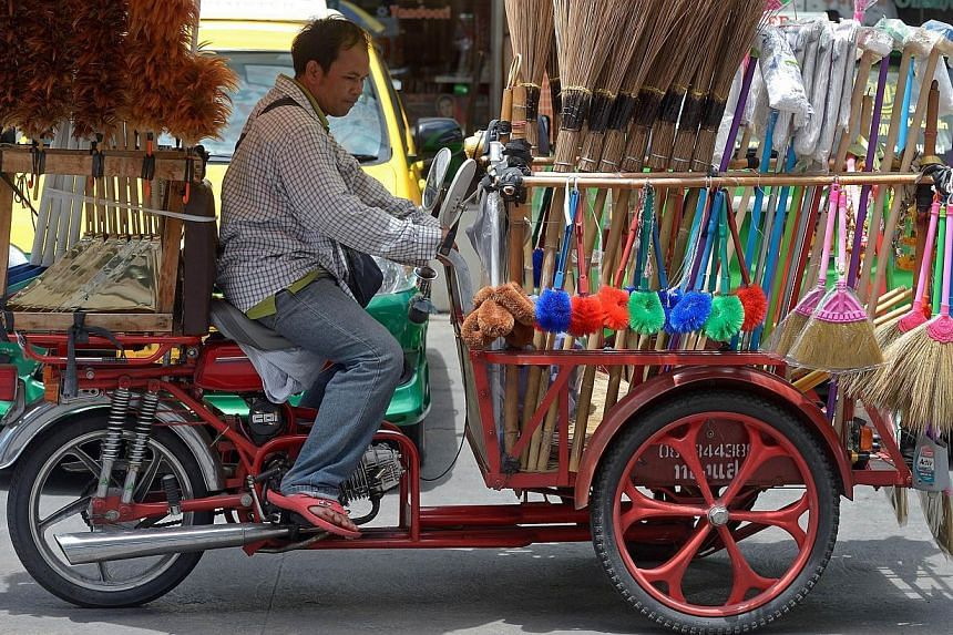 A Thai broom vendor riding a tricycle on the streets of Bangkok on Sept 1, 2014. In Thailand, Car Free Day is taking place in all 77 provinces, and in Bangkok, traffic police are sealing off parts or all of some major roads today and tomorrow. T