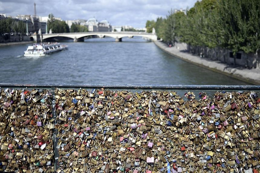 This picture taken on August 14, 2014 shows love padlocks attached on the railings of the Pont des Arts in Paris.City hall authorities are desperately trying to save the world-famous Pont des Arts and other bridges from damage from the thousand