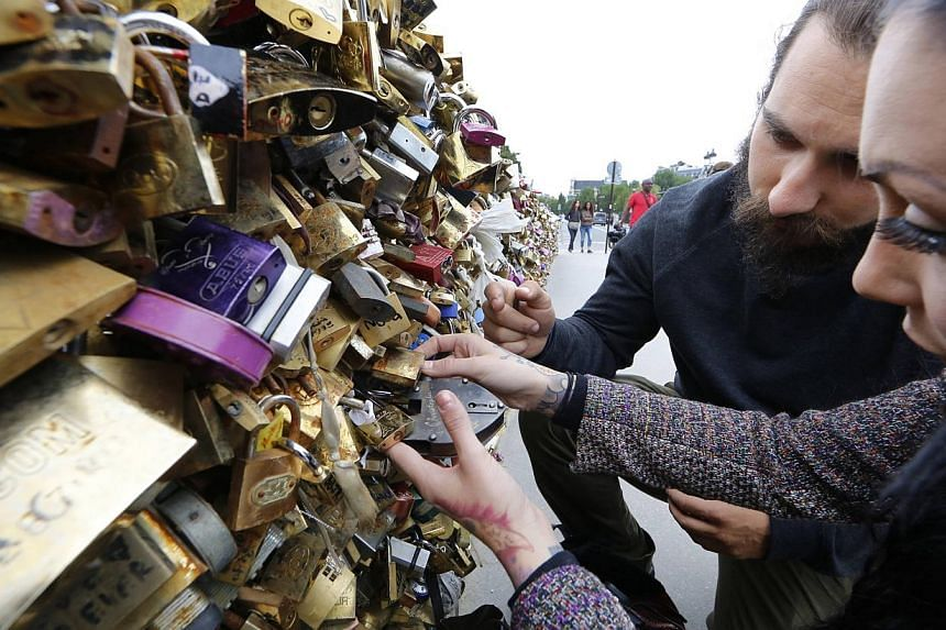 American tourists afix a love-lock on the Pont de L'Archeveche bridge, which is covered with thousands of padlocks near the Notre Dame Cathedral in Paris August 13, 2014. -- PHOTO: REUTERS