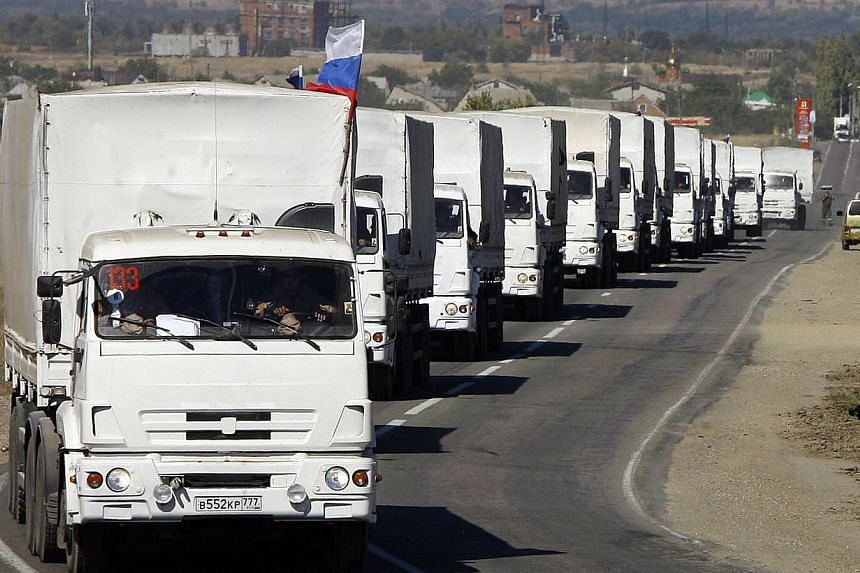 Lorries, part of a Russian humanitarian convoy, approach to the Ukrainian border at the Donetsk-Izvarino border checkpoint on Sept 19, 2014. -- PHOTO: AFP