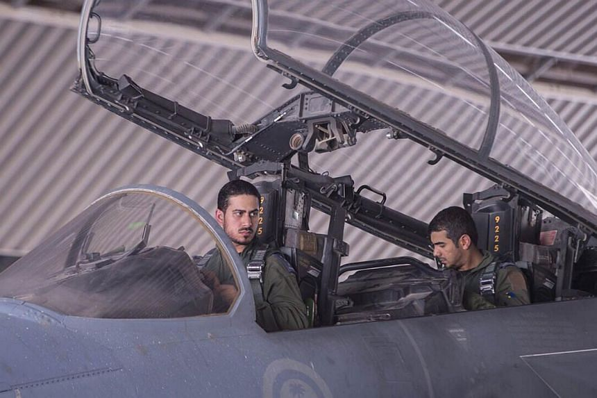 Saudi fighter pilots in their jet after a mission to strike ISIS targets in Syria on Tuesday. -- PHOTO: AFP