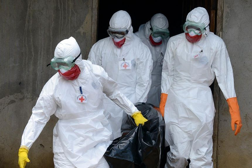 Medical workers of the Liberian Red Cross, wearing a protective suit, carry the body of a victim of the Ebola virus in a bag on Sept 4, 2014. -- PHOTO: AFP