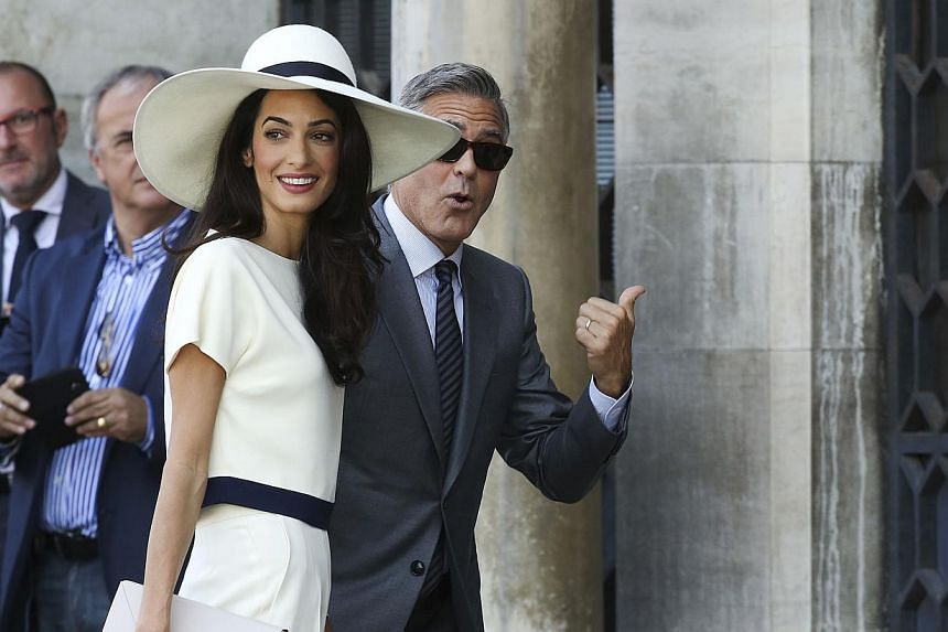 U.S. actor George Clooney and his wife Amal Alamuddin arrive at Venice city hall for a civil ceremony to formalize their wedding in Venice on Sept 29, 2014. -- PHOTO: REUTERS