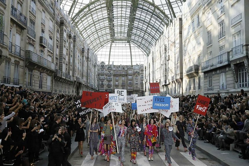 Models stage a demonstration as they present creations by German designer Karl Lagerfeld as part of his Spring/Summer 2015 women's ready-to-wear collection for French fashion house Chanel during Paris Fashion Week on Sept 30, 2014. -- PHOTO: REUTERS