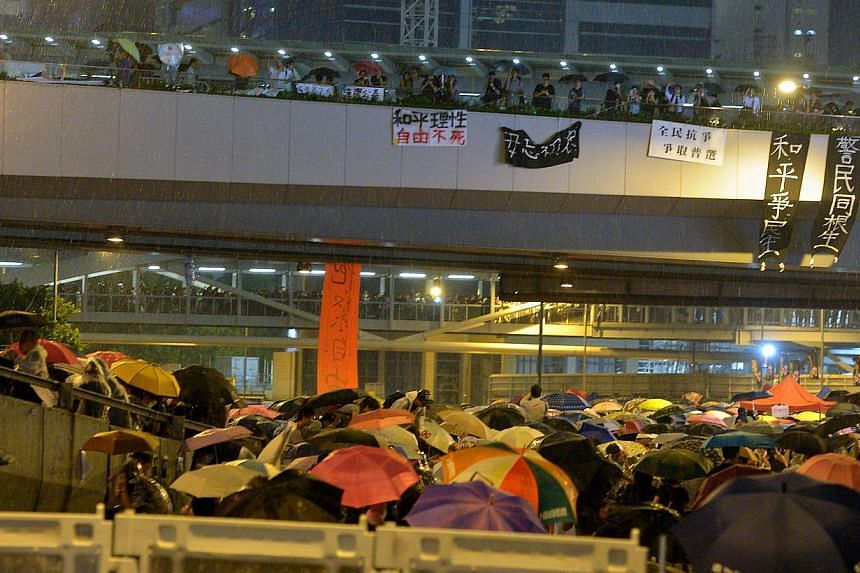 Umbrellas deployed during a sudden downpour as protesters block the road to the central business district in Hong Kong on Sept 30, 2014. -- ST PHOTO: KUA CHEE SIONG