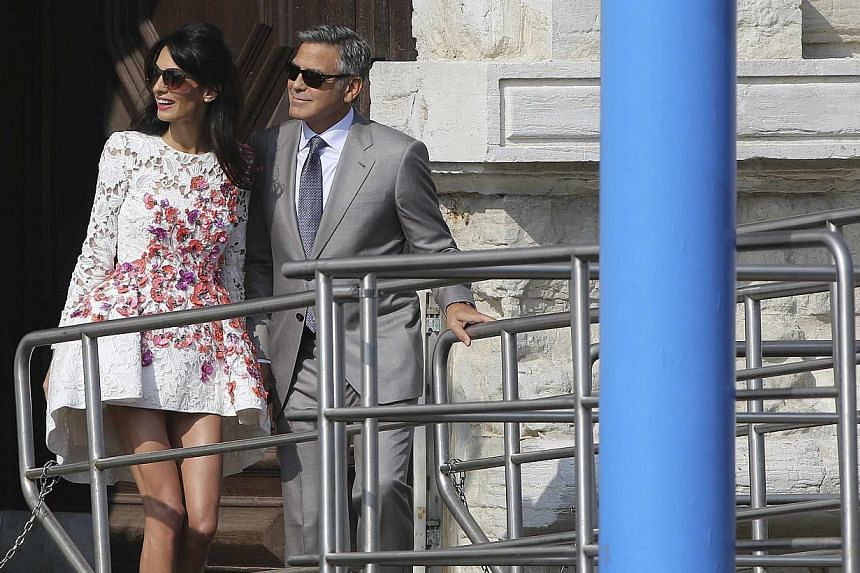 U.S. actor George Clooney and his wife Amal Alamuddin leave the seven-star hotel Aman Canal Grande Venice in Venice on Sept 28, 2014. -- PHOTO: REUTERS