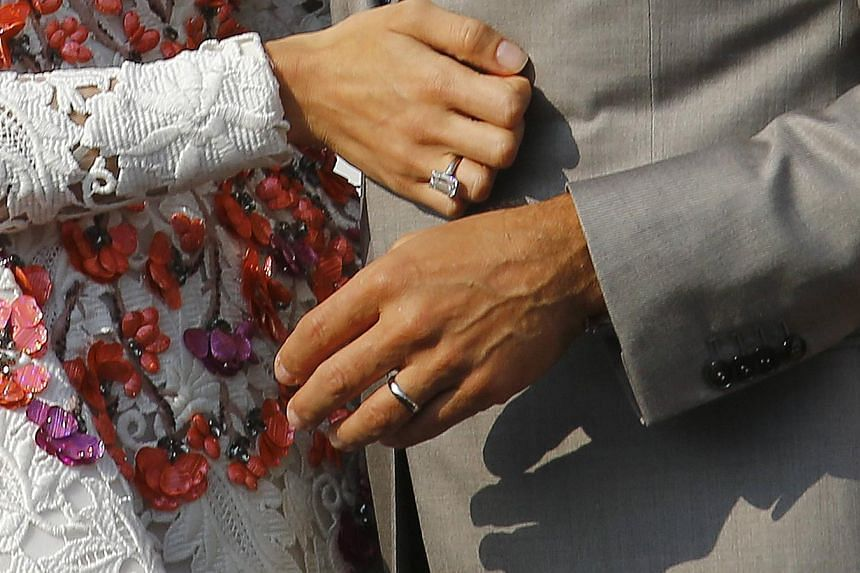 Wedding rings are seen on the hands of U.S. actor George Clooney (right) and his wife Amal Alamuddin as they stand in a water taxi on the Grand Canal in Venice on Sept 28, 2014. -- PHOTO: REUTERS