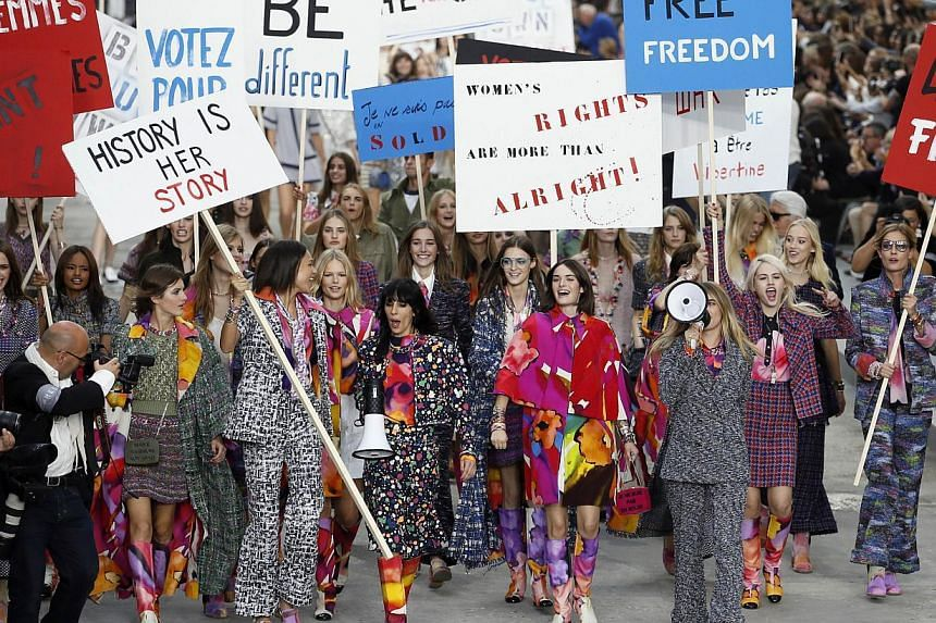 British model Cara Delevingne speaks through a megaphone (right) as she fakes a demonstration along with other models as they present creations for Chanel during the 2015 Spring/Summer ready-to-wear collection fashion show, at the Grand Palais in Par