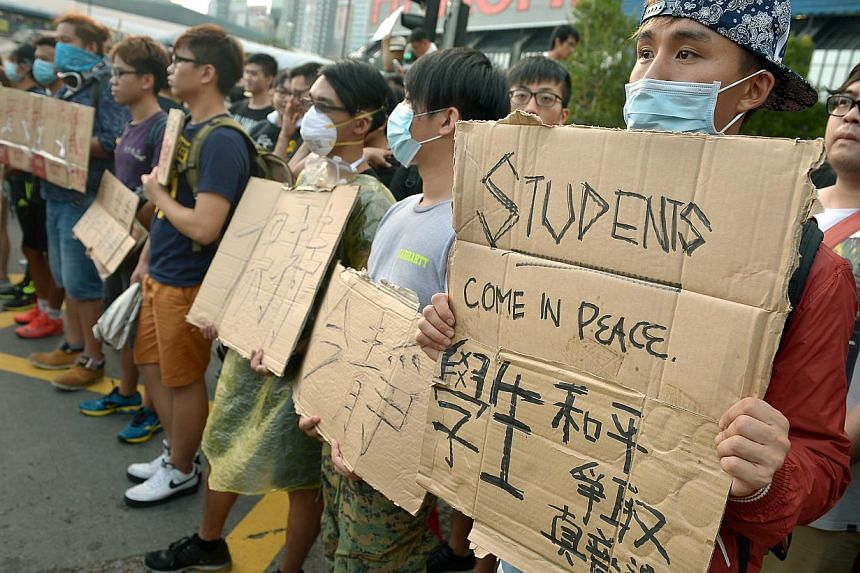 Protesters gathered outside the Hong Kong Convention and Exhibition Centre (HKCEC) in Wan Chai in support of student activist, Joshua Wong together with members of Scholarism on Oct 1, 2014. -- ST PHOTO: KUA CHEE SIONG