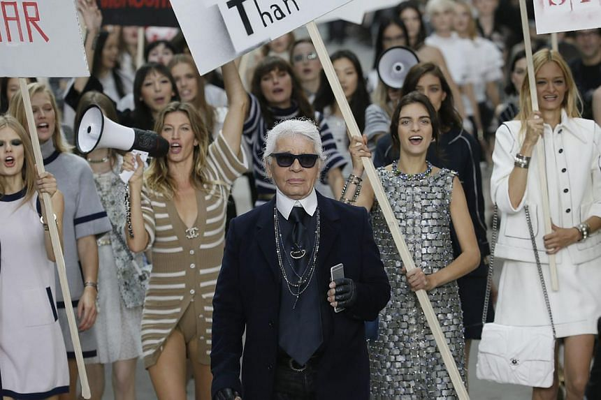 German designer Karl Lagerfeld appears with models who stage a demonstration at the end of his Spring/Summer 2015 women's ready-to-wear collection for French fashion house Chanel during Paris Fashion Week on Sept 30, 2014. -- PHOTO: REUTERS