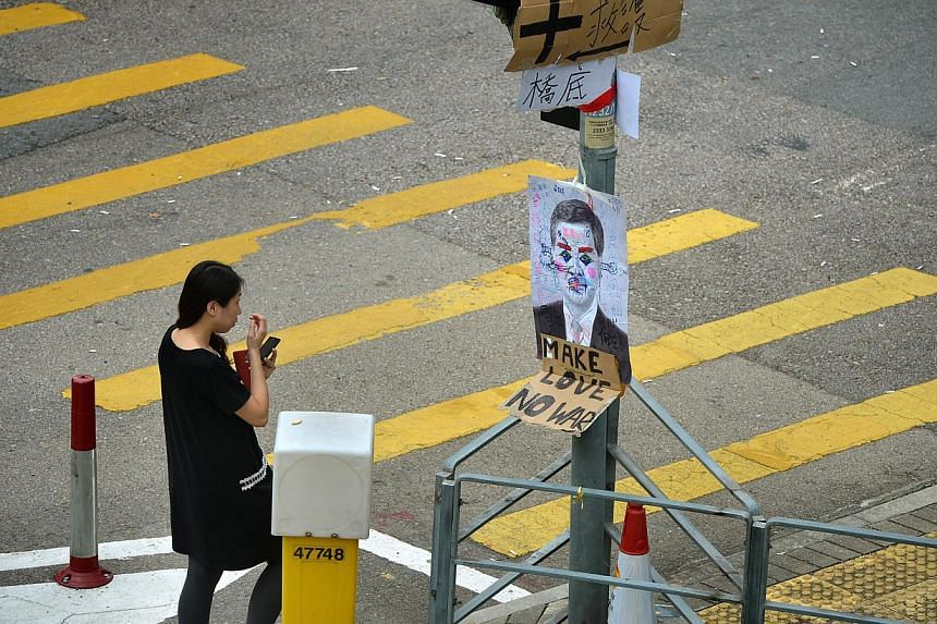 A woman walks past a defaced drawing of Hong Kong's Chief Executive Leung Chun Ying near the streets of the protest site of Harcourt Road on Sept 30, 2014.-- ST PHOTO: KUA CHEE SIONG
