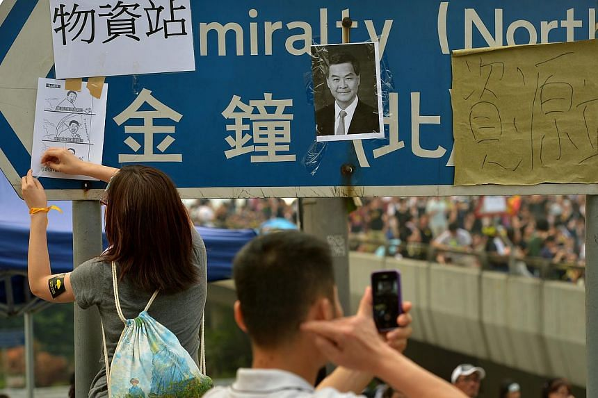 A woman pastes drawings among a picture of Hong Kong's Chief Executive Leung Chun Ying on the street sign near the streets of the protest site of Harcourt Road on Sept 30, 2014. -- ST PHOTO: KUA CHEE SIONG