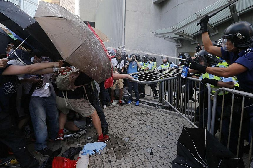 Protesters using umbrellas to block pepper spray from riot policemen, as tens of thousands of protesters block the main street to the financial Central district outside the government headquarters in Hong Kong on Sept 28, 2014. -- PHOTO: REUTERS&nbsp
