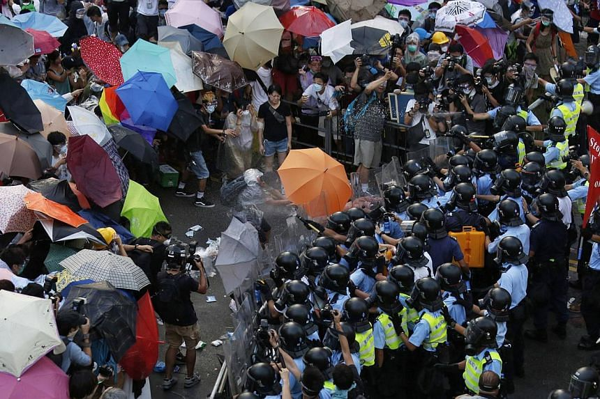 Protesters carrying umbrellas brave pepper spray used by riot police as tens of thousands of demonstrators block the main street to the financial Central district outside the government headquarters in Hong Kong on Sept 28, 2014. -- PHOTO: REUTERS&nb