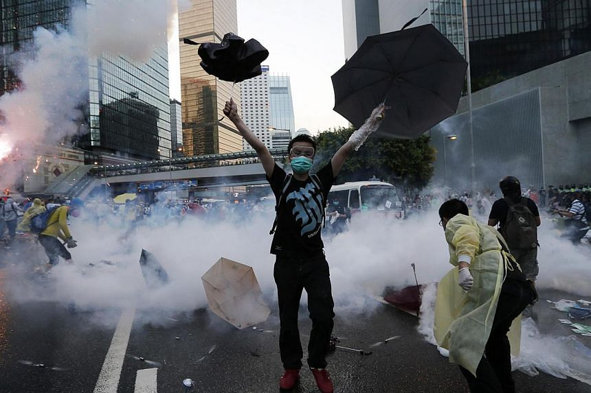 A protester raises his umbrellas in front of tear gas which was fired by riot police to disperse protesters blocking the main street to the financial Central district outside the government headquarters in Hong Kong, Sept28, 2014. -- PHOTO: REU