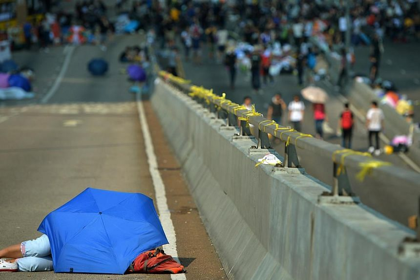 A female protestor sleeping under the shade of the umbrella in the morning sun along Connaught Road Central leading to Hong Kong's financial district, the heart of the protest in Hong Kong on Sept 30, 2014.-- ST PHOTO:KUA CHEE SIONG