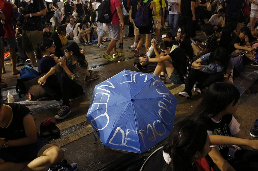 Protesters rallying next to an umbrella as they block the main road at Causeway Bay shopping district in Hong Kong on Sept30, 2014. -- PHOTO: REUTERS