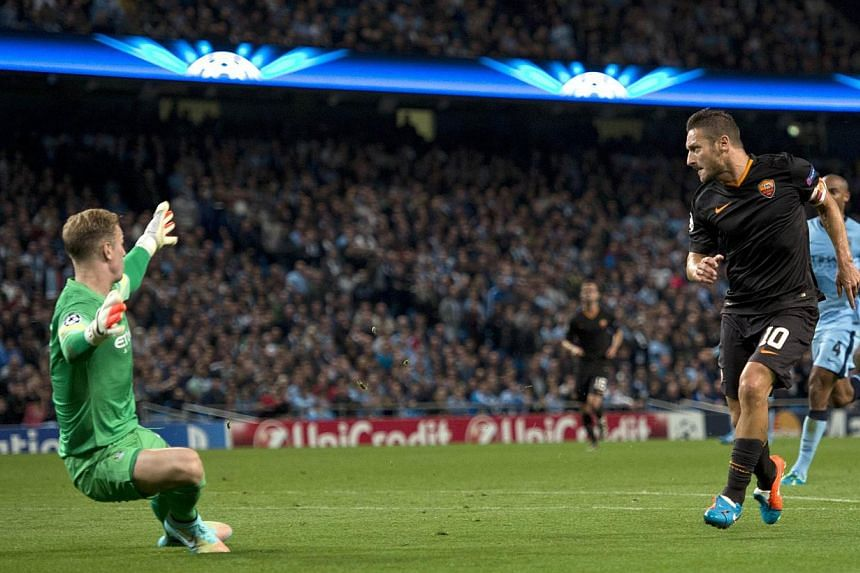 Roma's Italian forward Francesco Totti (right) scores the equalising goal past Manchester City's English goalkeeper Joe Hart (left) during the Champions League Group E football match between Manchester City and Roma in Manchester, Northwest England,