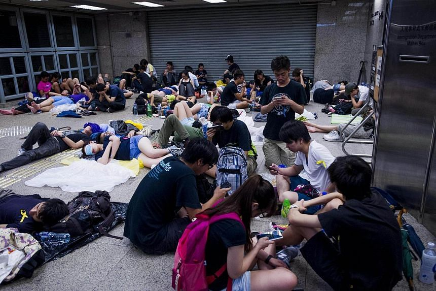 Pro-democracy demonstrators rest in an office building after overnight protests in the Wanchai district of Hong Kong on Oct 1, 2014.  -- PHOTO: AFP
