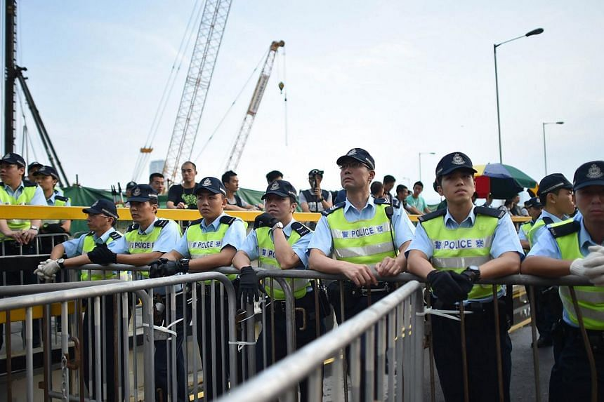 Police watch on from behind barricades as pro-democracy demonstrators gathered near a ceremony marking China's 65th National Day in Hong Kong on Oct 1, 2014.  -- PHOTO: AFP